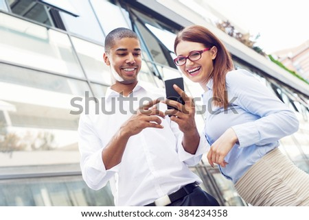 Business couple looking at smart phone and smiling. Shallow depth of field. - stock photo