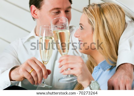 Business Couple - man and woman - at home with champagne sitting on stairs in their apartment - stock photo