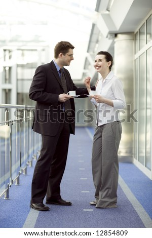 Business couple portrait - young man and woman having coffe on modern office corridor
