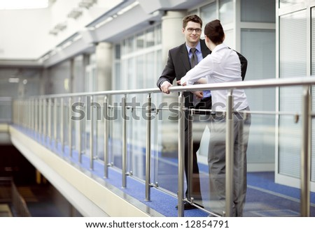 Business couple portrait - young man and woman standing and talking on modern office corridor - stock photo