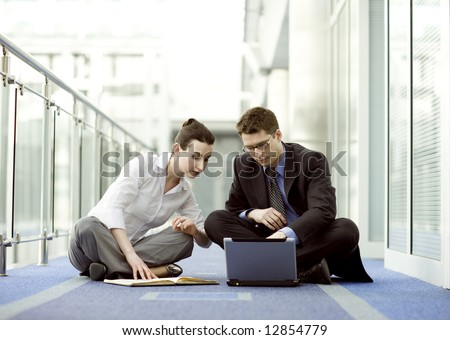 Business couple portrait - young man and woman working together on the floor - stock photo