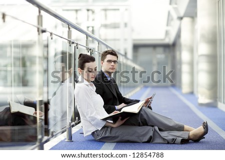 Business couple portrait - young man and woman working together on the floor of modern office corrdor