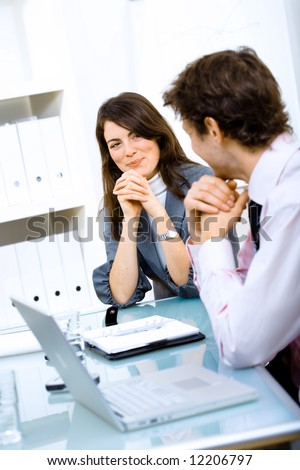Business couple sitting at table, looking at each other and smiling. - stock photo