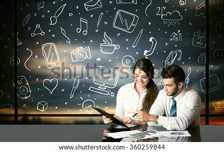 Business couple sitting at table with hand drawn social media icons and symbols  - stock photo