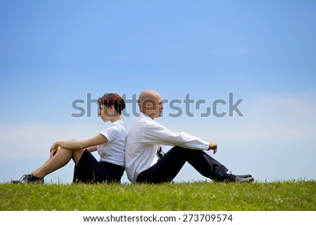 Business couple sitting back to back on grass - stock photo