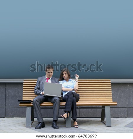 Business couple sitting on the bench - stock photo