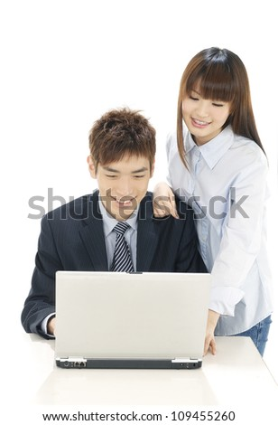 Business couple using laptop isolated over a white background - stock photo