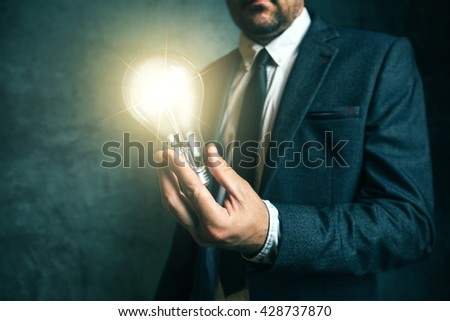 Business creativity and vision concept with elegant adult man holding bright light bulb as metaphor of new ideas - stock photo