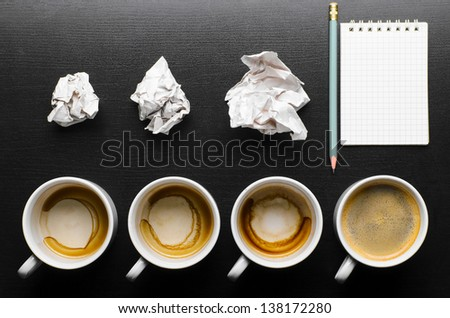 business creativity concept. empty and full cups of fresh espresso with crumple wads on desk - stock photo
