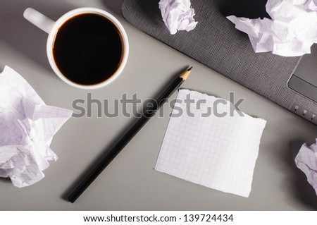 business creativity concept. Laptop, sheets of paper and crumpled wads on table. - stock photo