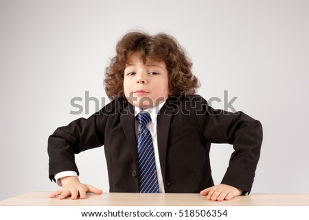 Business curly boy stands up from the table. Gray background. Close-up.