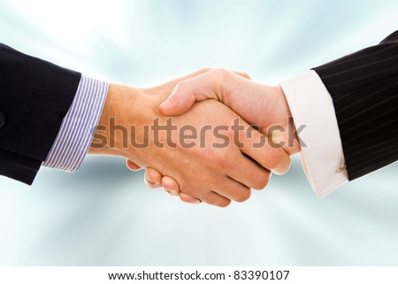 Business deal - Closeup of a handshake against blur background - stock photo