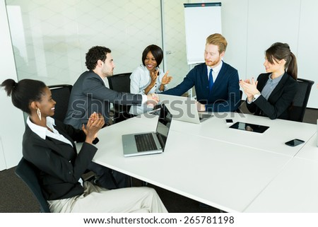 Business deal made between two businessmen in a neat office environment followed by a round of applause