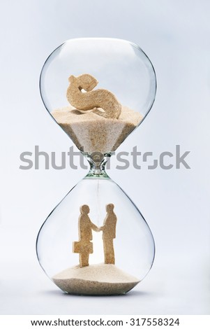 Business deal. Two businessmen shaking hands made out of falling sand from dollar sign flowing through hourglass