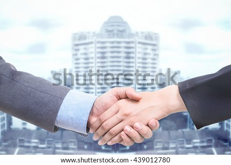 Business deal with handshake over big tower. - stock photo
