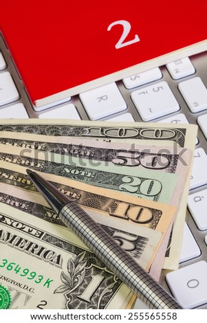 Business desk - Diary for February,US dollars,pen and keyboard - stock photo