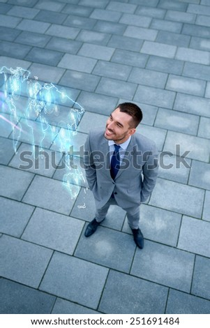business, development and people concept - young smiling businessman with world map hologram outdoors from top - stock photo