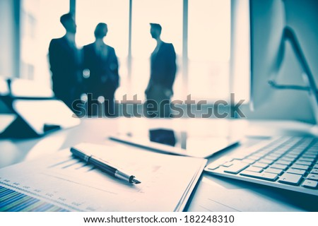 Business devices and documents at the workplace, unrecognized businesspeople sharing the ideas on the background  - stock photo