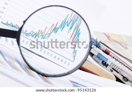 Business diagramme with magnifying glass, workplace businessman - stock photo