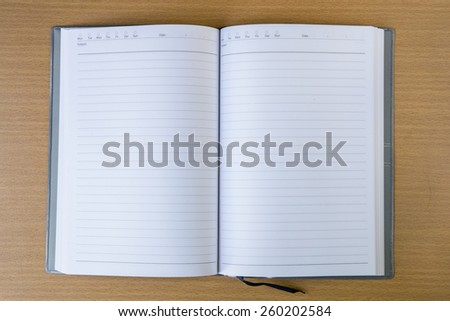 Business diary with a pen on wood table - stock photo