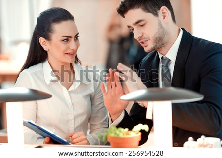 Business discussion. Closeup of handsome young man and woman looking at documents with marketing data while sitting at the restaurant - stock photo