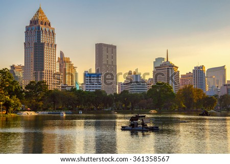Business district cityscape from a park with Sunset Time from Lumpini Park, Bangkok, Thailand