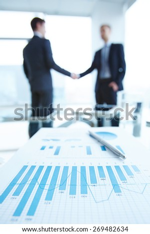 Business document with chart and graph on workplace with two men handshaking on background - stock photo