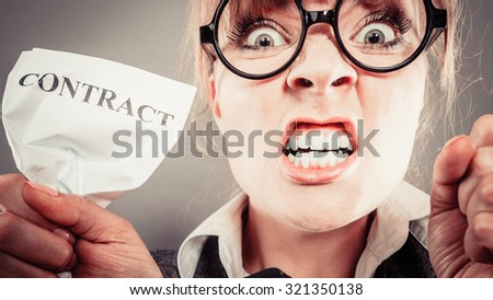 Business, documents and legal concept - Angry mad unhappy businesswoman holds crumpled contract - stock photo