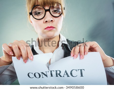 Business, documents and legal concept - serious unhappy businesswoman tearing crumpled contract - stock photo