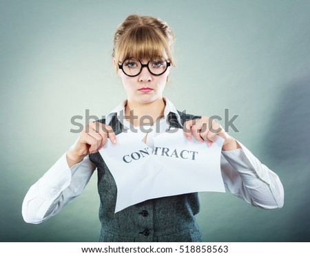 Business, documents and legal concept - serious unhappy businesswoman tearing crumpled contract