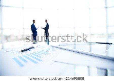 Business documents and pen at workplace on background of businessmen interacting - stock photo