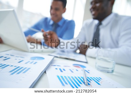 Business documents, glass of water and pen with two businessmen on background