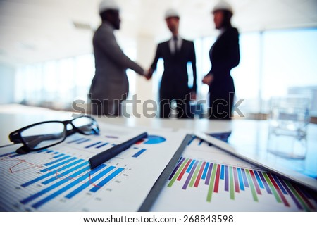 Business documents on background of three business partners - stock photo