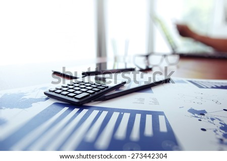 business documents on office table with calculator and digital tablet and man working in the background - stock photo