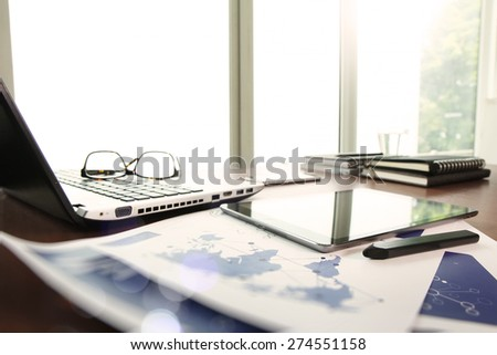 business documents on office table with laptop and digital tablet as work space business concept - stock photo