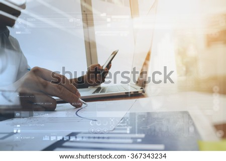 business documents on office table with laptop computer and digital graph business diagram and man working in the background - stock photo