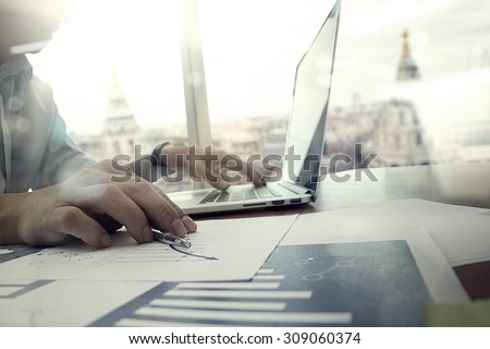 business documents on office table with laptop computer and graph business diagram and man working in the background - stock photo