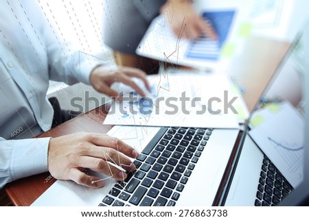 business documents on office table with laptop computer and two colleagues discussing data  and graph business diagram  in the background - stock photo