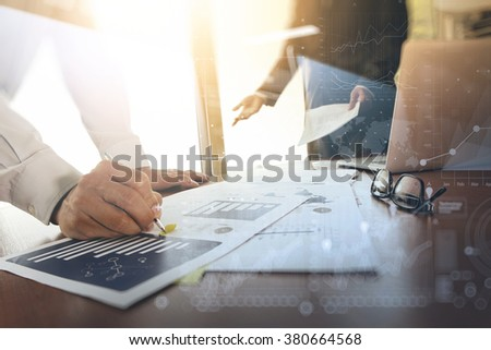 business documents on office table with smart phone and blank screen laptop computer and graph business diagram and two colleagues discussing data in the background - stock photo
