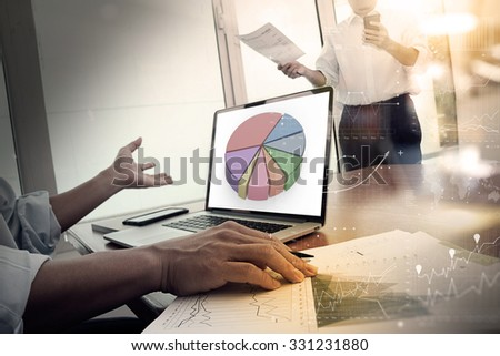 business documents on office table with smart phone and digital laptop computer and two colleagues discussing data in the background - stock photo