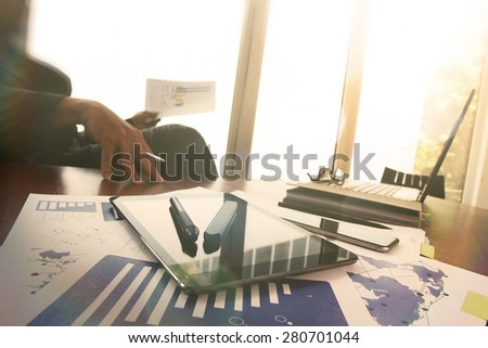 business documents on office table with smart phone and digital tablet and graph business diagram and man working in the background - stock photo