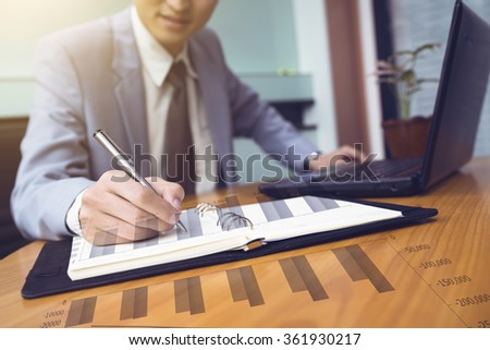 business documents on office table with smart phone and digital tablet and graph business with social network diagram and man working