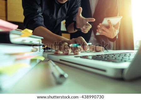 business documents on office table with smart phone and digital tablet and graph business with social network diagram and two colleagues discussing data working in the office  - stock photo