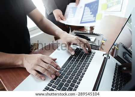 business documents on office table with smart phone and digital tablet and laptop computer and two colleagues discussing data in the background
