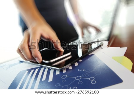 business documents on office table with smart phone and digital tablet and man working in the background - stock photo