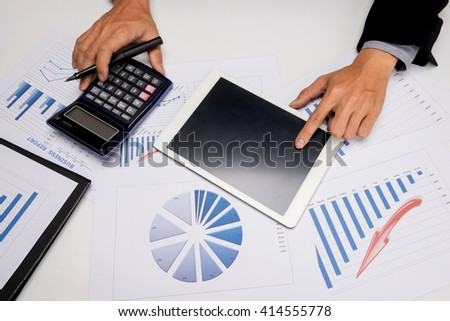 business documents on office table with smart phone and digital tablet and man working in the background. - stock photo