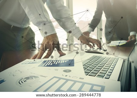 business documents on office table with smart phone and digital tablet and stylus and two colleagues discussing data in the background - stock photo