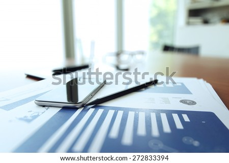 business documents on office table with smart phone and digital tablet as work space business concept