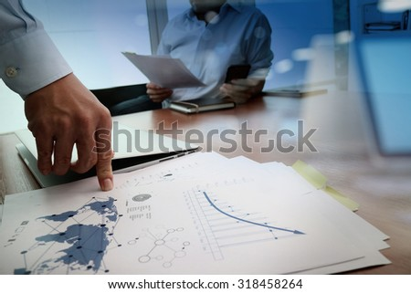business documents on office table with smart phone and laptop and two colleagues discussing data in the background  - stock photo