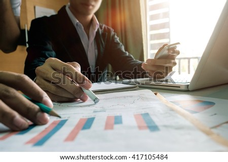 business documents on office table with smart phone and laptop and two colleagues discussing data in the background in morning light